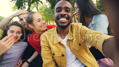Glückliche Freunde machen Kamera betrachtenden, sprechenden und lachenden den on-line-Videoanruf, während Afroamerikanermann hält