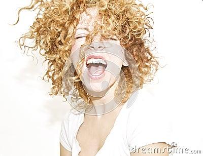 Glückliche junge Frau mit dem unordentlichen lockigen Haar