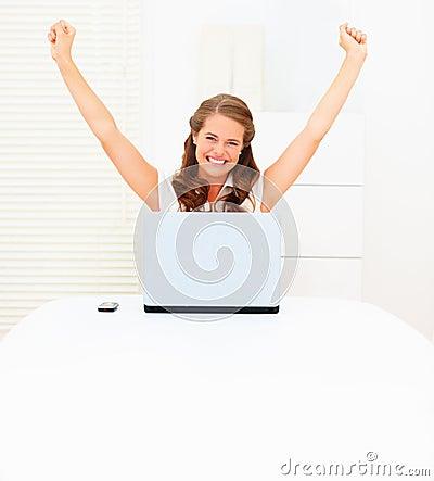 Glückliche junge Geschäftsfrau, die einen Laptop verwendet