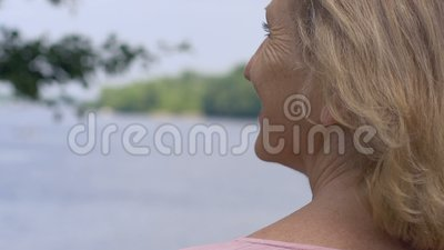 Glückliche lächelnde alte Frau, die in der Natur sich entspannt und oben See, Abschluss betrachtet stock footage