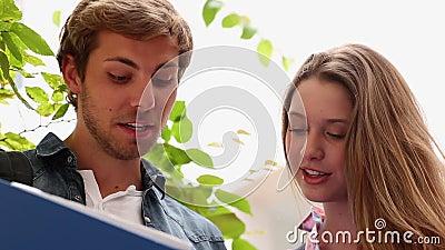 Glückliche Mitschüler, die zusammen Tablette betrachten stock video footage