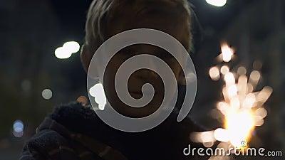Glücklicher Junge, der beleuchteten Feuerwerksschein am Weihnachtsabend, Feier mit Familie hält stock video