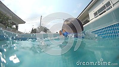 Glücklicher kleiner Junge taucht unter Wasser im Schwimmbad ein Ein Unterwasserschuss stock video footage