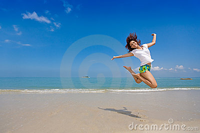 Glücklicher Sprung des Mädchens am Strand