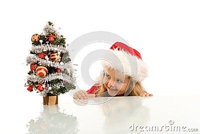 Glückliches Kind, das um einen kleinen Weihnachtsbaum lauert