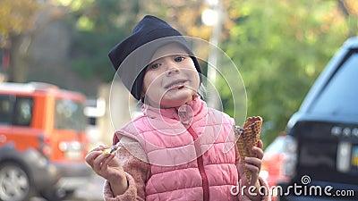 Glückliches Mädchen, das SchokoladenEiscreme mit einem Waffelkegel, köstlichen Nachtisch isst stock footage