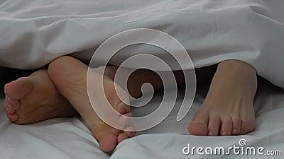 Glückliches Paar, das Liebe im Bett, Beine vom Ehemann und Frau, vertraute Beziehungen macht stock video