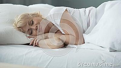 Glückliches weibliches Schlafen von mittlerem Alter im Bett auf orthopädischer Matratze, Gesundheit stock video footage