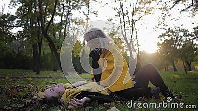 Glad barndom, en ung mor med en söt dotter har kul i höstens ängsskugga i parken på gräs, bladfall lager videofilmer