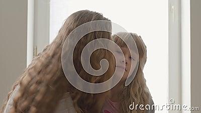 Glad blond caucasisk mor som kramar sin irriterade lilla dotter hemma Begreppet moderskap, barndom, en förälder stock video