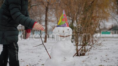 Glad flicka bygger en snöman i vinterparken Begreppet vintersemestrar och julklappar stock video