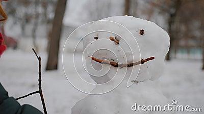 Glad flicka bygger en snöman i vinterparken Begreppet vintersemestrar och julklappar lager videofilmer