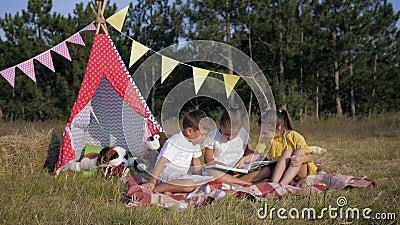 Glad tid, barn med charm som klappar sina händer glatt och dricker mjölk på picknick under sommarhelgen på lager videofilmer