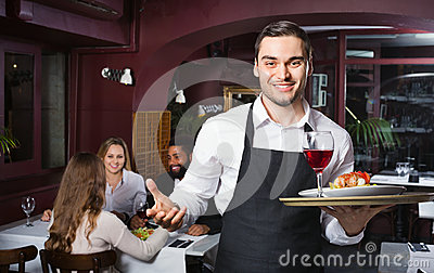 Glad young waiter taking care of adults