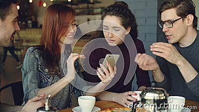 Gladlynta unga män och kvinnanära vänner använder smartphonen och talar, medan ha lunch i trevligt kafé äta middag arkivfilmer