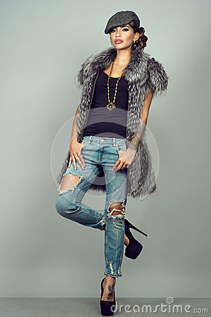 Free Glam Tattooed Model With Provocative Make-up Wearing Silver Fox Jacket, Ripped Blue Jeans, High-heeled Shoes And Peaked Cap Royalty Free Stock Photo - 79740455