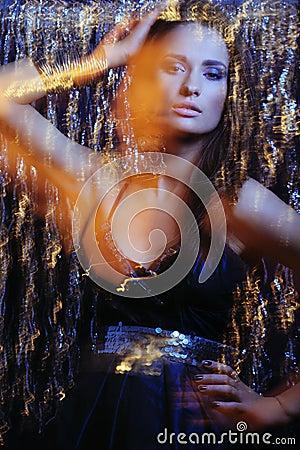 Glamor girl in black dress in motion lights