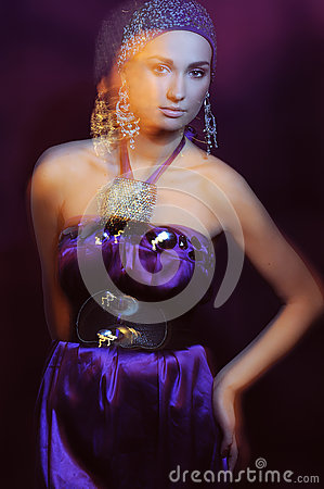 Glamor girl in violet evening dress in motion blur