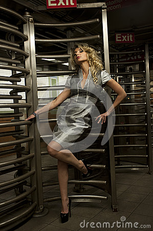 Glamor model standing by entrance with revolving door to subway