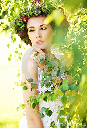 Glamorous brunette lady among greenery