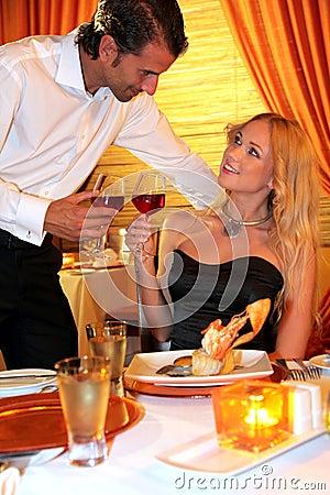 Glamorous couple cheering in restaurant