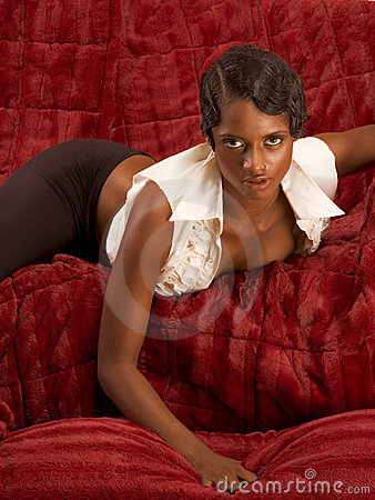 Glamorous sexy retro ethnic woman lying on couch