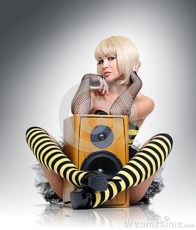 Glamorous sexy young girl with wooden speaker