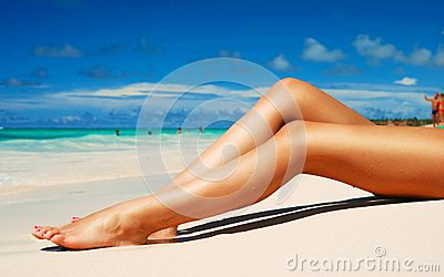 Glamorous woman with perfect legs relaxing on beac