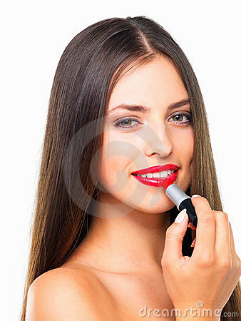 Glamorous young woman applying lipstick