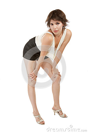 Glamorous young woman stands with hands on knees.