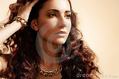 Glamour model with shiny gold jewelry, volume hair