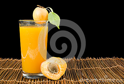 Glass apricot juice and fruits black .