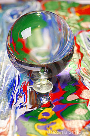 Glass ball on colorful surface
