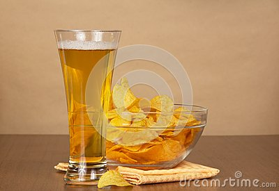 Glass of beer, bowl with chips and a napkin