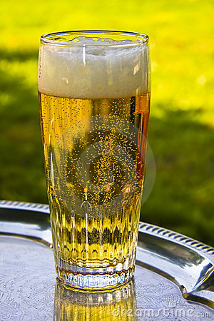 A glass of beer silver on a tray