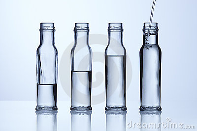 ... life shot of glass bottles with different levels of clear water fluid