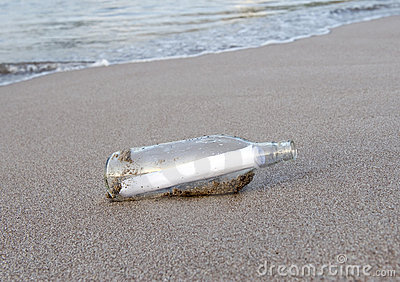Glass bottle with note message on tropical beach