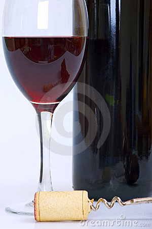 Glass and bottle of red wine with cork and corkscrew