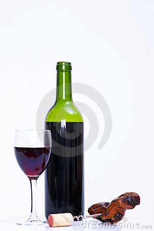 Glass and bottle of red wine and corkscrew
