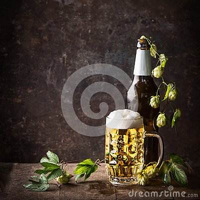 Free Glass Bottles And Mug Of Beer With Cap Of Foam And Hops On Table At Dark Rustic Background, Front View, Still Life Royalty Free Stock Image - 101471506