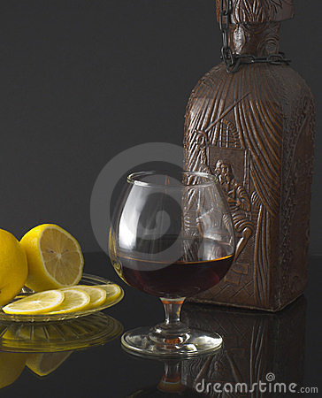 Glass of cognac, bottle and lemon