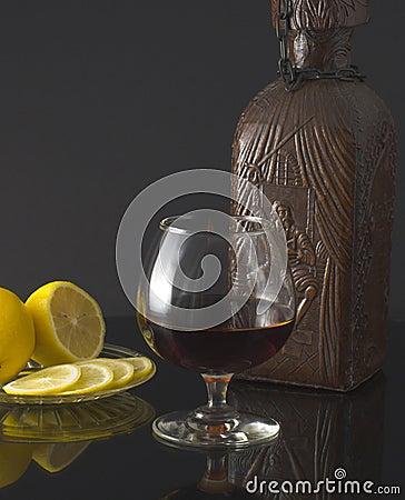 Glass of cognac, bottle and lemon