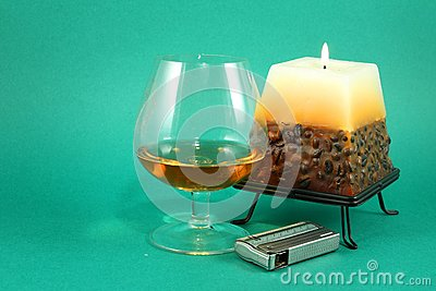 Glass of cognac and burning cand