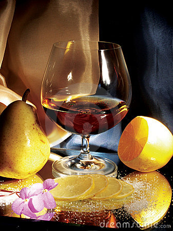 Glass of cognac with lemon and pear