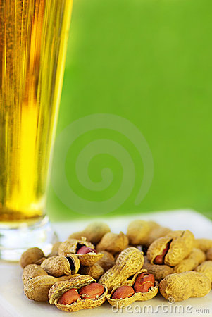 Glass of cold beer with peanuts