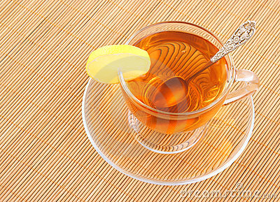 Glass cup of tea with spoon and lemon