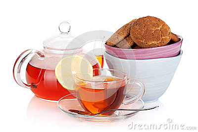 Glass cup and teapot of black tea with lemon and cookies