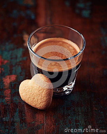 Glass of espresso with heart-shaped biscuit