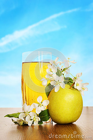 Glass of fresh apple juice on wooden surface against blue sky
