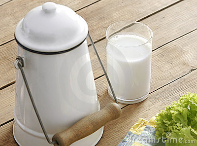 Glass of fresh milk and old milk-churn